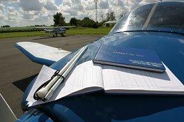 Une canne blanche et un livre de carte en braille sur le nez d'un avion